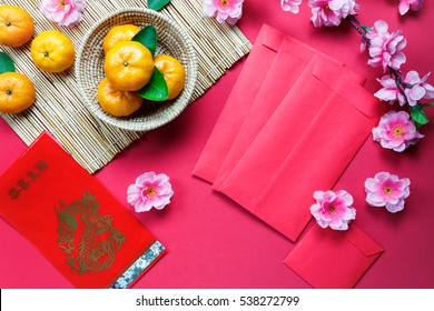 Top view accessories Chinese new year festival decorations.orange,leaf,wood basket,red packet,plum blossom on red background.Foreign language means be rich and Happy.