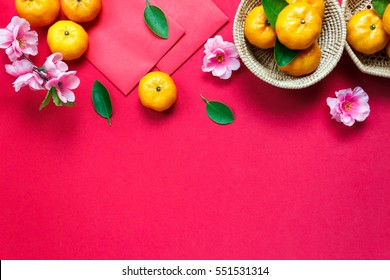 Top view  accessories Chinese new year festival decorations.orange,leaf,wood basket,red packet,plum blossom on red background.
