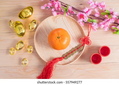 Top view accessories Chinese new year festival decorations.orange,leaf,wood dish,red packet,plum blossom, on wood background