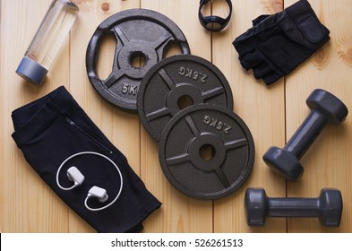 Top view of accessories for fitness in black grey tone. Dumbbells, weight plates,  gloves for gym, sport watch,music player and bottle of water on wooden background. Concept for sport or workout.