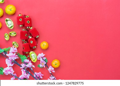 Top view accessories on Lunar New Year & Chinese New Year vacation concept background.Orange with red lantern and pink flower on modern rustic red paper backdrop.Other language mean rich or wealthy.