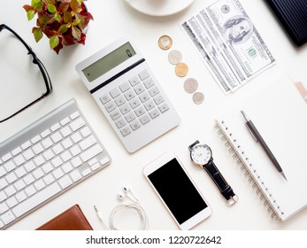 top view of accounting concept with keyboard, smartphone, notebook, coffee cup, calculator and money on white table background.