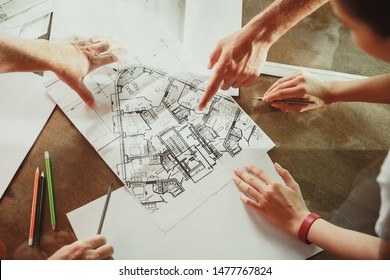 Top view of achitect-engineer's hands shows future house, office or store design plans to a young couple. Meeting at the construction office to talk about facade, interior decoration, home layout.