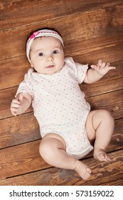 Top view of adorable baby girl looking at camera while lying on wooden background