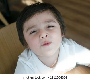Top view of adorable boy sending kiss with closing eyes, Portrait Cute kid sitting on chair in cafe looking up with smile face, Preschool kid showing kiss to parent