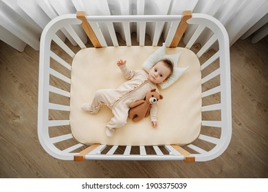Top view of adorable infant in stylish pajama lying on pillow crown in comfortable cot at home. Baby with teddy bear in cradle in baby's room