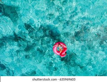 Draufsicht auf bezaubernde kleine Mädchen, die auf den Malediven im tropischen Meer schwimmen