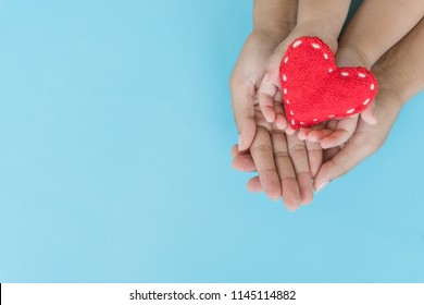 Top view of adult and child holding red heart in hands, Happy family relationships, Valentine's day, Mother's Day, Love and health care concept.
