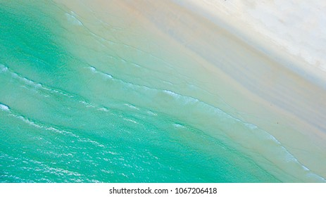 Top view or Aerial view of beautiful sand beach with the emerald water creating ripple curving endless wave.Beach background holiday vacation concept