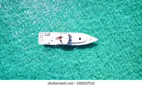 Top view aerial of couple enjoying sunbathing on the roof of luxury boat moving in a sea