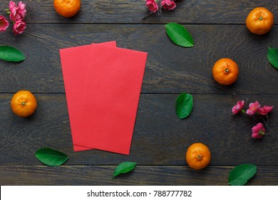 Top view aerial image of accessory decoration Chinese new year & lunar holiday background concept.Flat lay Orange & flower also red pocket money.Variety object on modern brown wood at office desk.