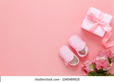 Top view aerial image of decoration Happy mothers day holiday background concept.Flat lay gift box with rose & baby shoe on modern beautiful pink paper at home office desk.Free space for design.
