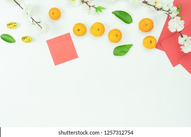 Top view aerial image shot of arrangement decoration Chinese new year & lunar new year holiday background concept.Flat lay  orange with red pocket money on modern white wooden at home office desk.