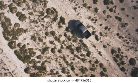 Top view aerial photo from drone of farmer pickup machine riding in Texas rural for check his farmland. Journey to america on rental car in desert valley landscape. Beautiful photo for travel website