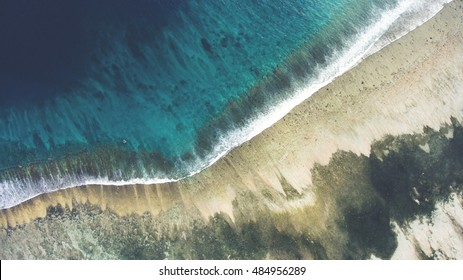 Top view aerial photo from flying drone of a beautiful sea scenery with coral bottom and volcanic sandy beach with copy space. Wonderful nature wallpaper with Indian Ocean landscape