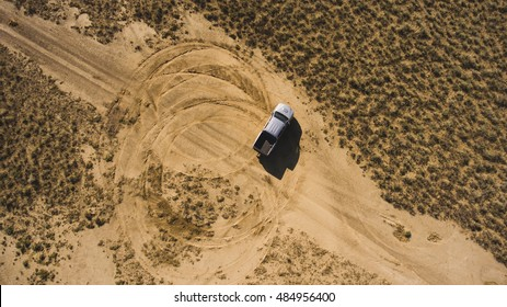 Top view aerial photo from flying drone of a professional driver having dangerous ride with pickup car in desert landscape. Active extreme sport leisure with automobile in arid steppe in sunny day
