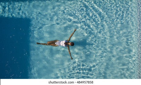 Top view aerial photo from flying drone of a seductive sexy model in white swimwear is enjoying relax in hotel pool during her summer weekend. Amazing fashion woman in bikini having luxury spa rest