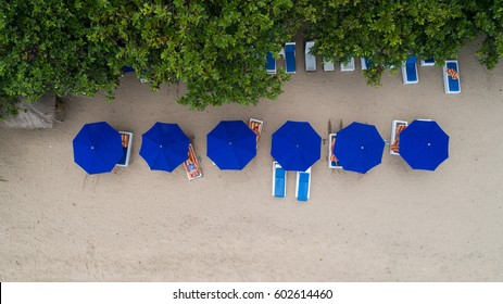Top view aerial photo from flying drone of seats and umbrellas, Kuta beach, Bali.