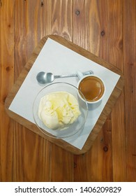 Top view of affogato coffee; espresso shot served with vanilla ice cream on white paper and wood tray on wooden table; one of the dessert from coffee; shoot from mobile camera.