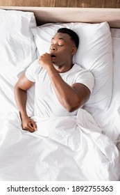 Top view of african american man yawning on bed