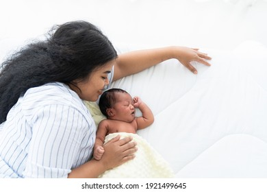 Top view African American mum lying with her newborn baby on the bed. Closeup of infant with mother. Woman and adorable little African American baby on bed