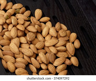 Top view of almond nuts in a wooden tray