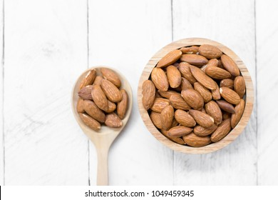 Top view of almonds baked in a wooden bowl are placed on a white wooden floor.