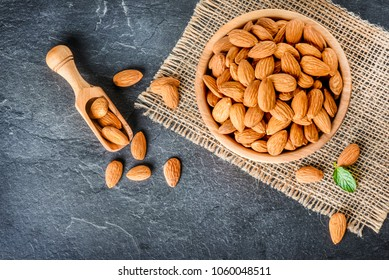 Top view of almonds on dark stone talbe with wooden spoon or scoop. Almonds in wooden bowl. Almonds laid freely on dark table.