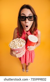 Top view of amazed young woman in 3d glasses holding popcorn and cola, looking at camera, isolated on yellow background