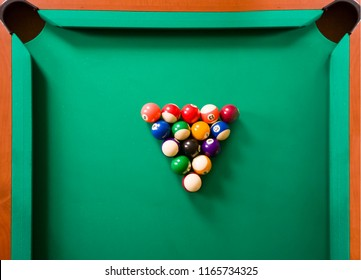 Top view of an American billiard (snooker) pool on a green table isolated with balls and cues.