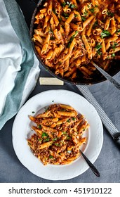 Top view of american chop suey - pasta dish with beef, tomato sauce, mozarella cheese, spices and parsley. Italian-American cuisine