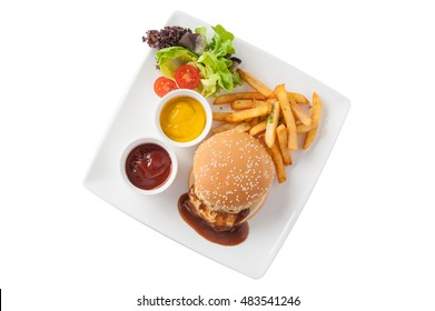 Top view of American style barbecue pork burger set including french fries, ketchup, mustard sauce, garnished with fresh vegetables in ceramic dish isolated on white background