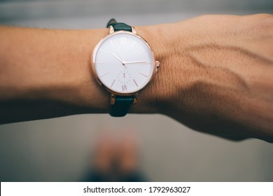 Top view of analog watch with Roman numerals as casual accessory on crop hand of young female demonstrating exact time on blurred background