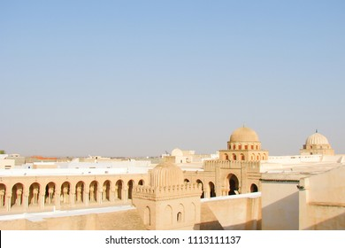 top view of ancient domes and courtyard of the Mosque of Uqba, blue sky over flat roofs of the Arab city, sultry evening in summer, Tunisia