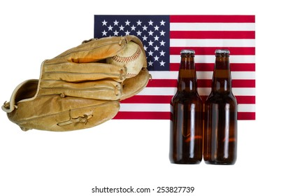 Top view angled shot of worn leather mitt, used baseball and full beer bottles with United States of America flag in background isolated on white.