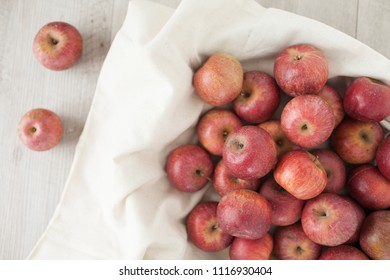 Top view of Annurca apples, cultivated in Southern Italy, typically at the border between the Caserta and Benevento provinces, in the valley which is called the queen of apples. Wooden background.