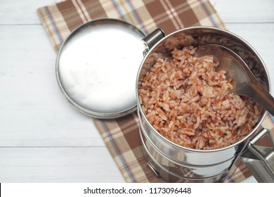 Top view of Antique stainless steel food carrier or Tiffin food container and spoon on wood background. Brown rice. Set breakfast, lunch or dinner. Still life food.Free space for text. Simple style.