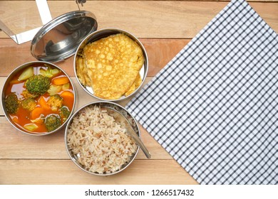 Top view of Antique stainless steel food carrier (Tiffin food container) and spoon on wood table. Omelette (Omelet), Vegetable sour soup and Brown rice. Set of food. Lifestyle.