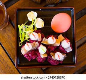 Top view of appetizer of pickled herring with onions, grated beets served on slices of toasted rye bread. Russian cuisine