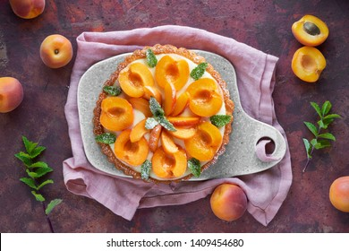 Top view of apricot tart with mint leaf on ceramic board with linen towel on dark red textured background