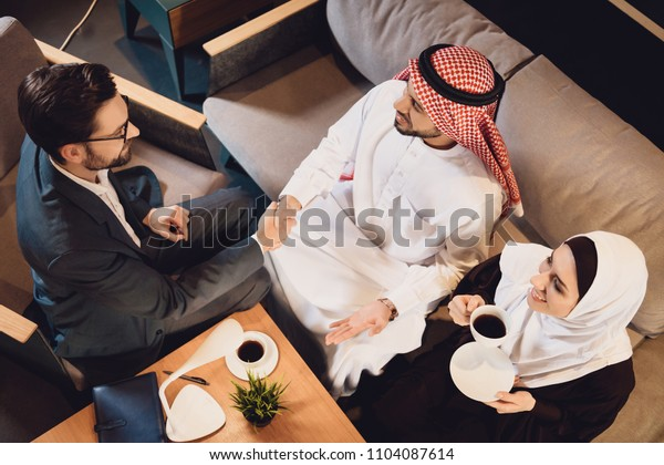Top view. Arab man shakes hands with psychotherapist. Reception at psychologist. Visiting psychotherapist concept