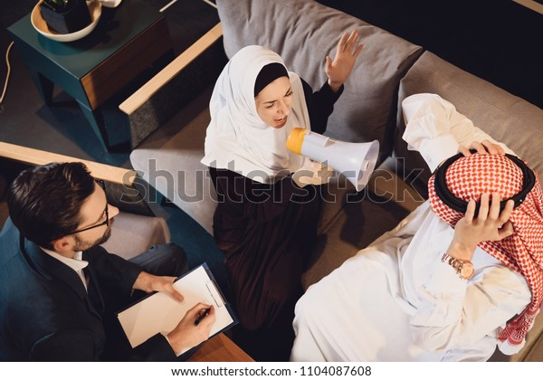Top view. Arab woman screams into megaphone at reception of psychotherapist.Arab couple. Visit to psychotherapist.