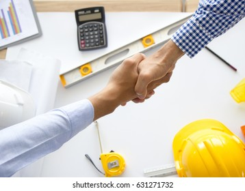 Top view Architect and the engineering contractor shaking hands on building project, tools background.