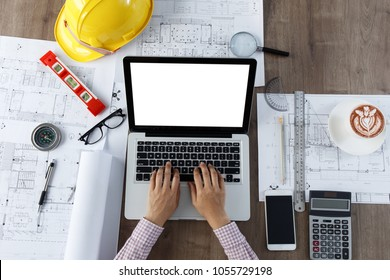 Top view, an architect hands using laptop with a building of blueprint and engineering tools on working table.