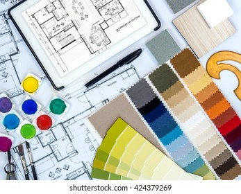 Top view of architect, interior designer worktable with with fabric swatch, tablet computer, sketch, blue print & sample / Real estate business & home renovation  conceptual