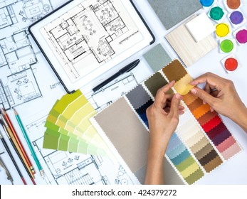 Top view of architect & interior designer working at worktable with fabric swatch, tablet, sketch & blue print/ Real estate business & home renovation conceptual