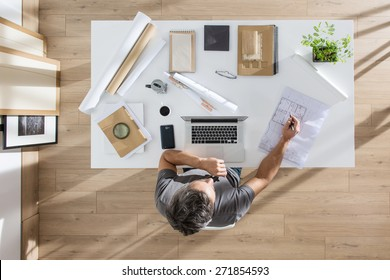 top view, architect sitting at  desk and working on his laptop, there is blueprints and model house on his table, the sun casts graphics shadows on the wood floor