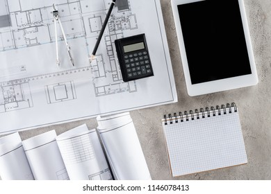 top view of architect workplace with blueprint, divider and digital tablet with blank screen