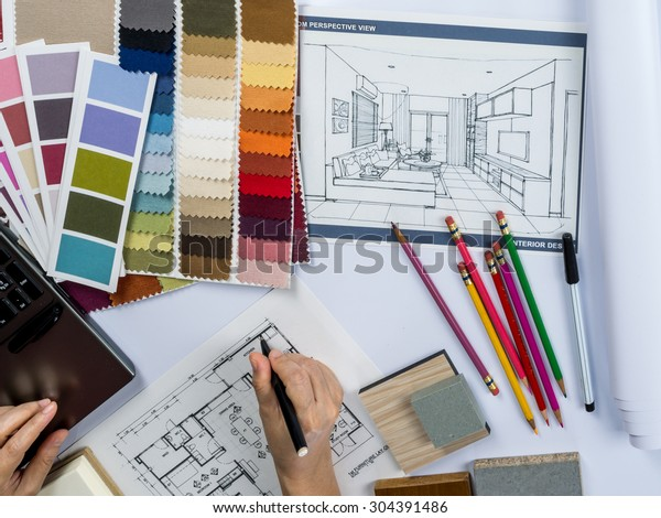 Top view of architects hands drawing of modern house with material sample on creative desk