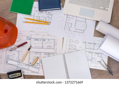 Top view of architect's workplace with project, laptop and rolls
